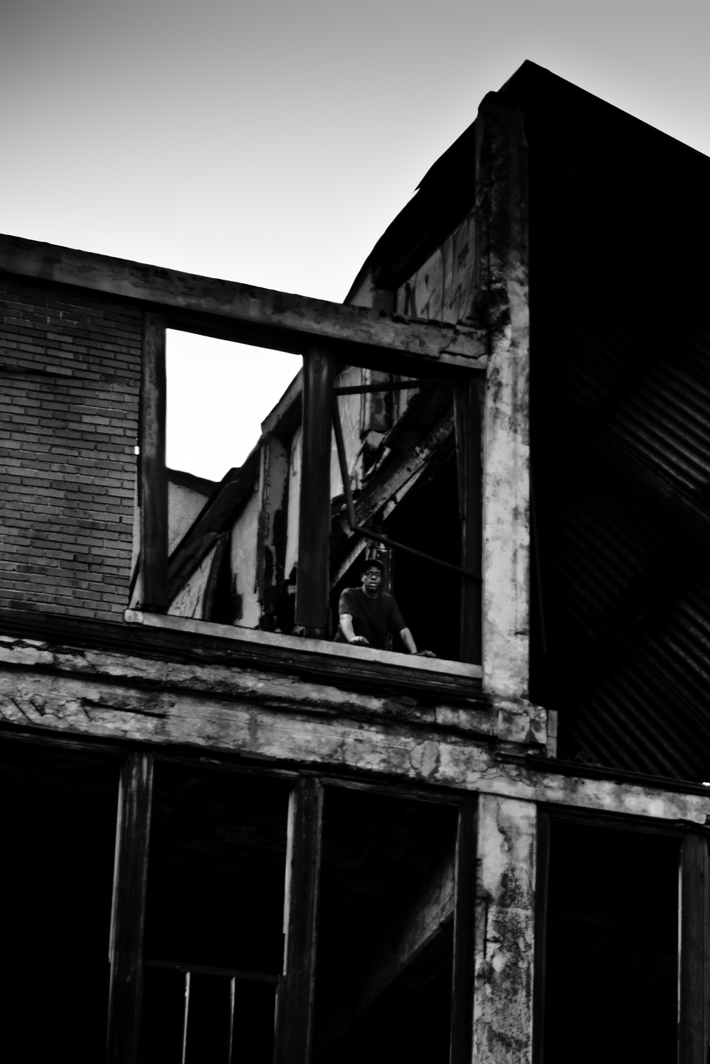 A scrapper looks down from the fifth floor of the Packard Plant to speak to his partner. Packard Plant, Detroit.