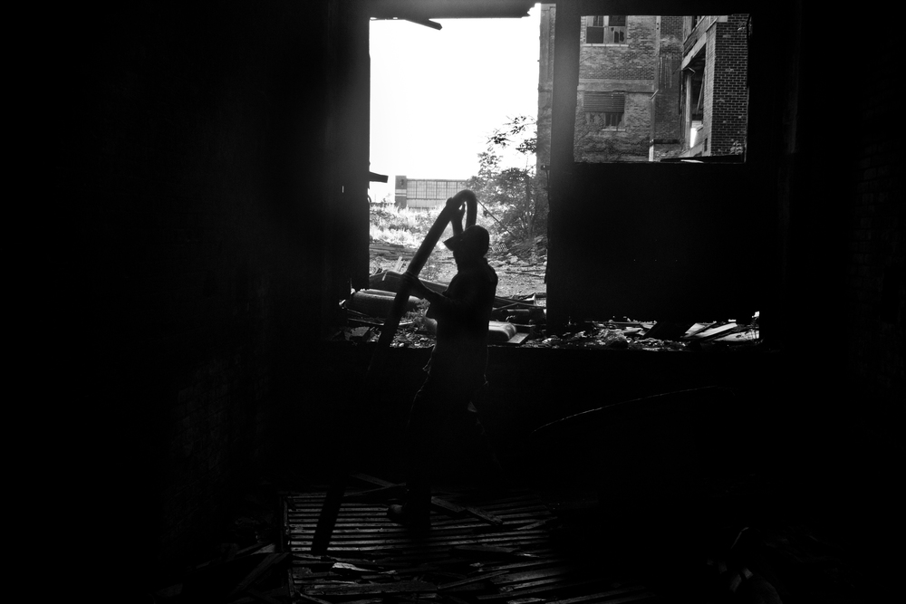 A scrapper lifts heavy metal out of an abandoned elevator shaft  at the Packard Plant, Detroit.
