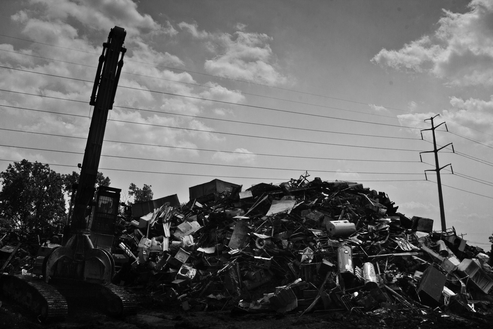 Purchased metal of all types stacked into piles before it is sorted, recycled, and then exported. Many scrapyards deal primarily with industry scrap metal in order to avoid the legal issues surrounding individual scrappers.  H&H Metals, Detroit.