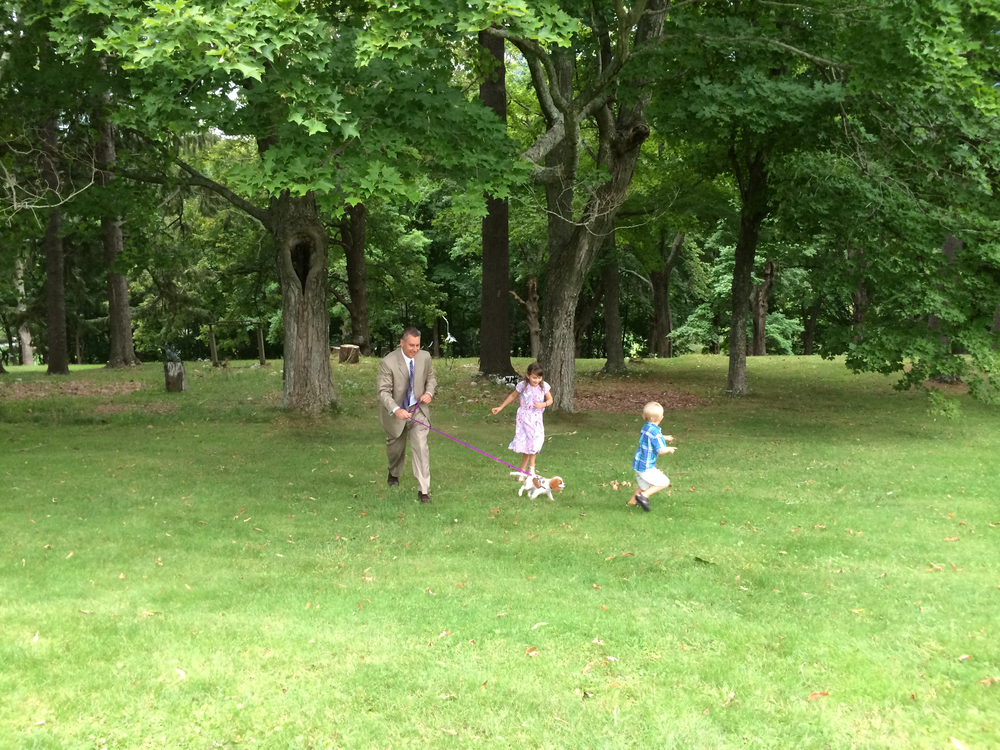 Dad and kids walk dog on lawn.jpg