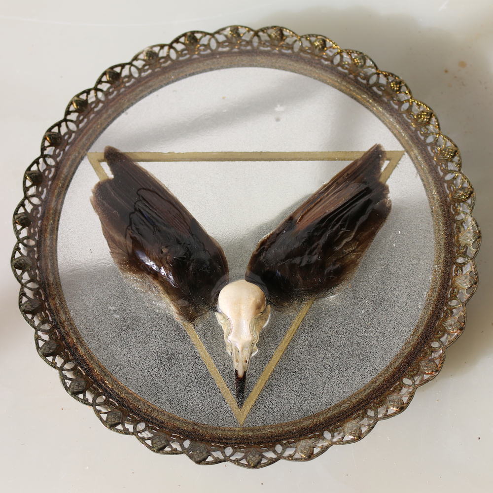 "Delta , mirror, bird skull and wings, gold enamel, resin, approx. 8x8"", 2015."