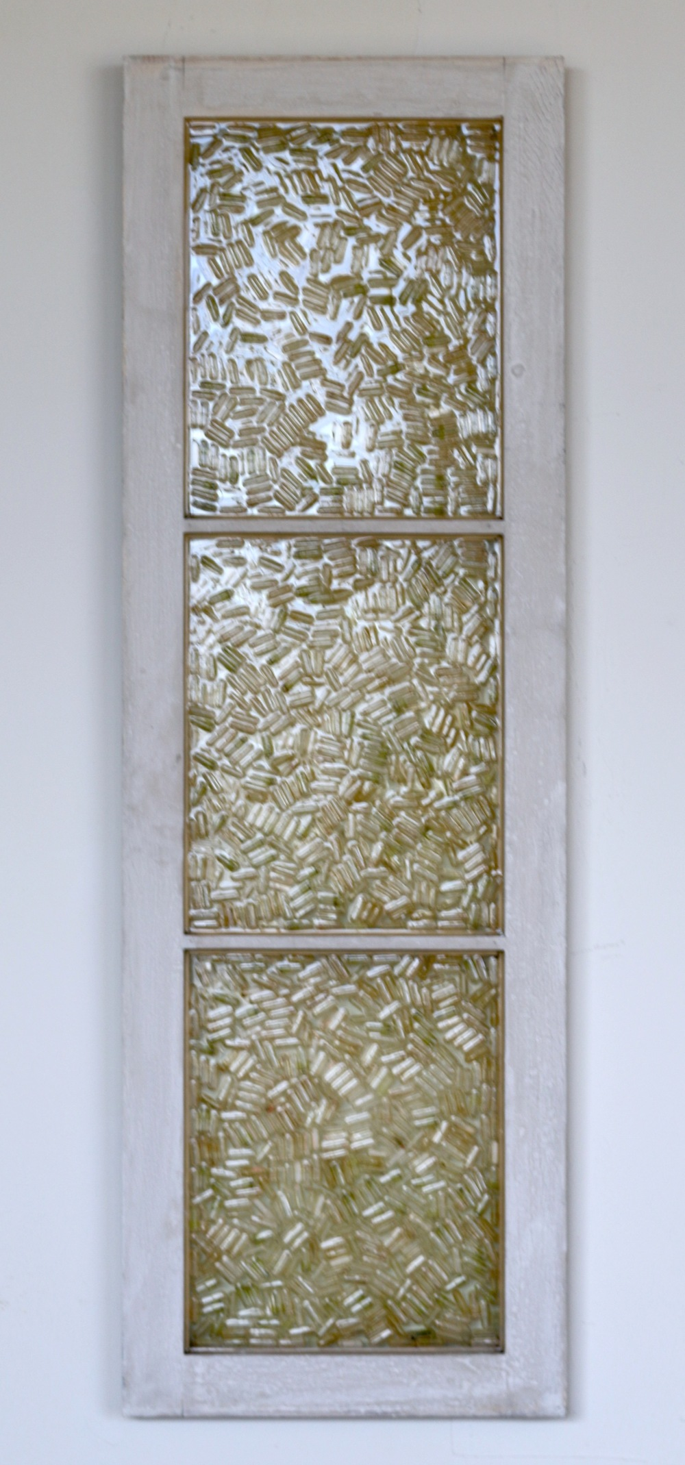 "Making Space, Filling it Up,  empty pill capsules, window, resin, 14.75""x45"", 2015"