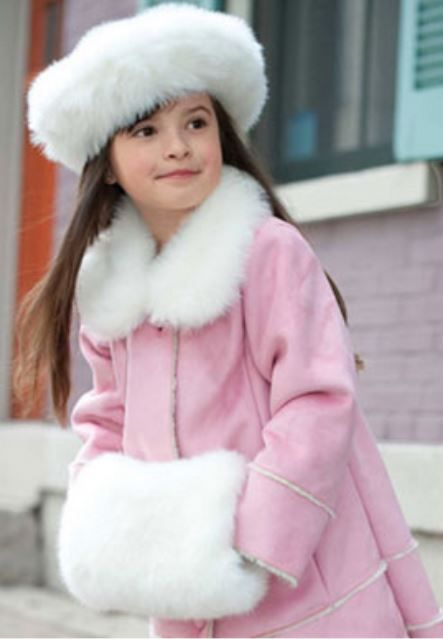 Little girl keeping warm and looking adorbs with her faux fur muff