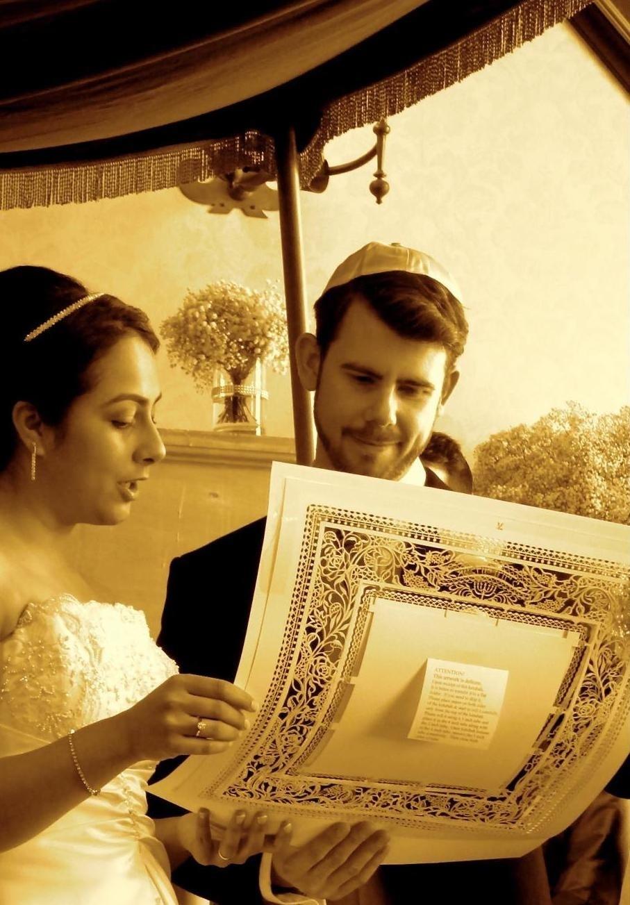 A couple holding their Ketubah
