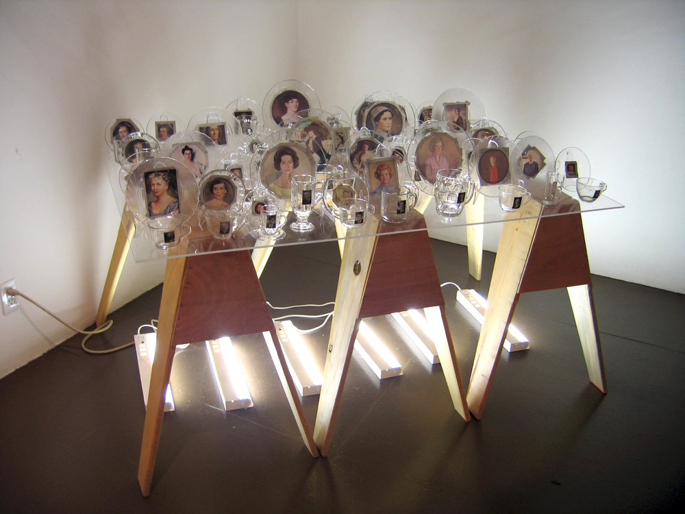 First Love (Installation at Shared Women LACE), 2007, Glass, paper, tape, plexiglass, wood and fluorescent lights 41 cups with president, 41 saucers with first lady, 4 x 3 x 3'