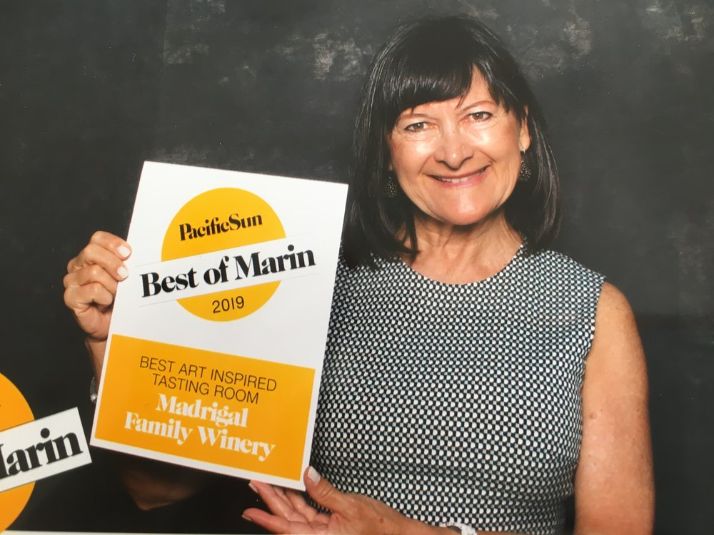 """Patricia Gatti, Manager of Madrigal Family Winery Sausalito Wine Salon & Gallery Accepts 2019 Pacifid Sun Best of Marin Award  for """"Best Art Inspired Tasting Room"""". She began the Madrigal Art & Wine  Series program with Curator Shiva Pakdel in October 2015."""