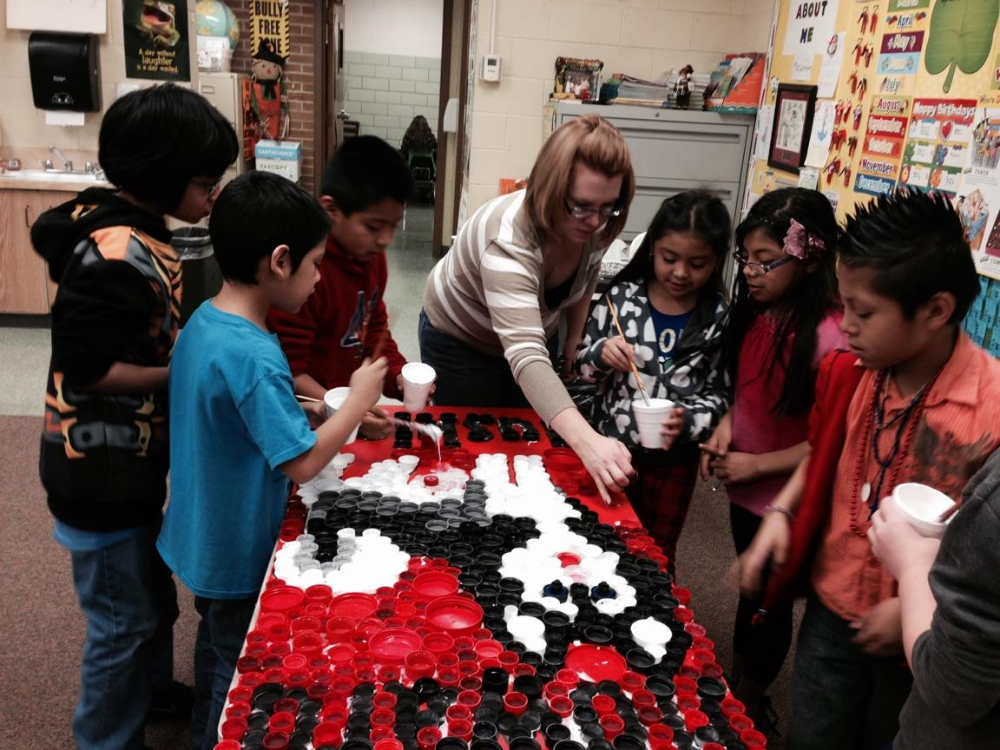 Keep GI Beautiful Coordinator Holli assisting Howard Elementary 2nd graders in assembling a recycled bottle cap art project.