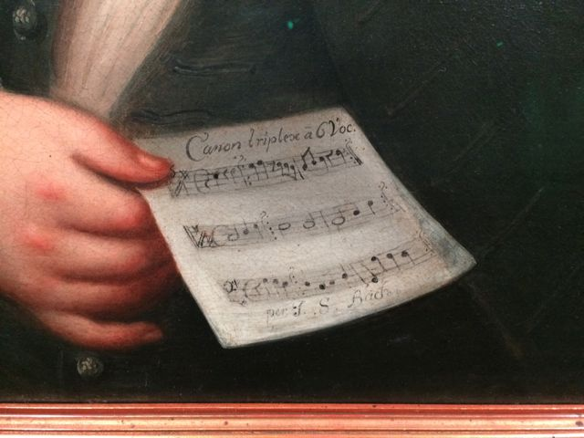 ...He is holding a code book for a canon in 6 voices; three are provided and the other three are to be solved.