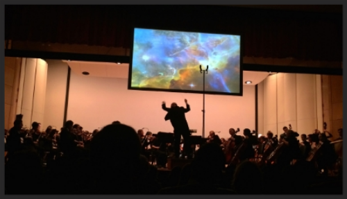 Jed Gaylin conducting the Hopkins Symphony Orchestra in Cosmic Dust Read Science News: Celebrating 25 Years of the Hubble Space Telescope