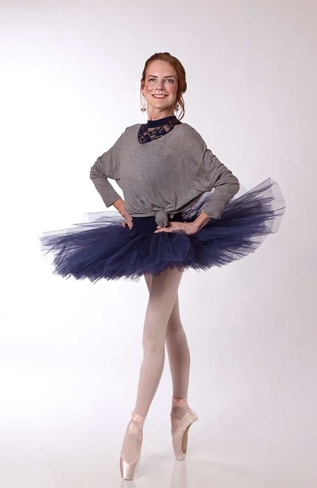 Carol wears the  Scarlett Leotard  and  Half Tutu  in Navy, with the  Studio Pullover  in Grey Marle and Energetiks  Sapphire  Pointe Shoes