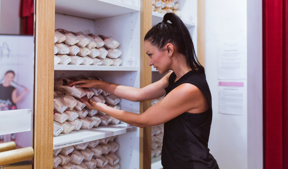 Nicole with the Ivanhoe Pointe Shoe Wall, which features all of the styles of pointe shoes available during a fitting.