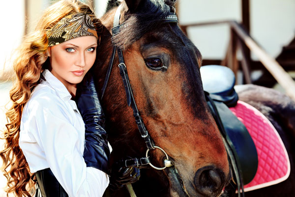 beautiful lady with brown and black paisley headband next to expensive big horse