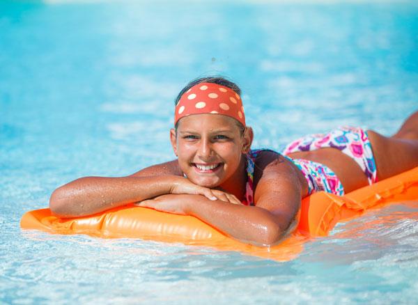 Girl on a pool float in bikini wearing headband
