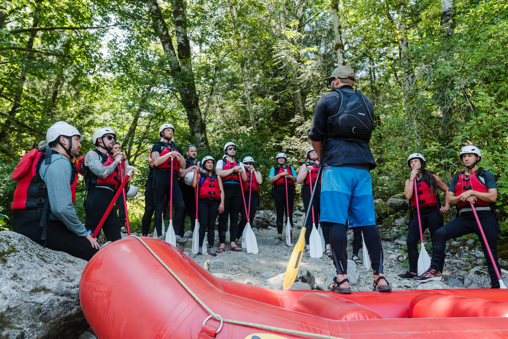 Lead Guide Blake Henderson takes a crew of rafters on the Skykomish through an in depth safety briefing before challenging the rapids of the Sky.