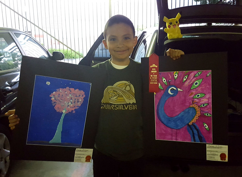 Young Parker and his buddy pikachu stand proudly with his paintings that each earned red ribbons at this year's imaginology exhibition at the orange county fairgrounds. (The cherry blossom tree on the left is his favorite painting to date.)