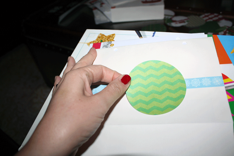 Here's the larger circle being glued on - try to mix middle, left, right, high, and low placement.  Oh!  And remember that the holes are punched at the bottom of the envelope, so you should use the bottom edge as your top.  Does that make sense?