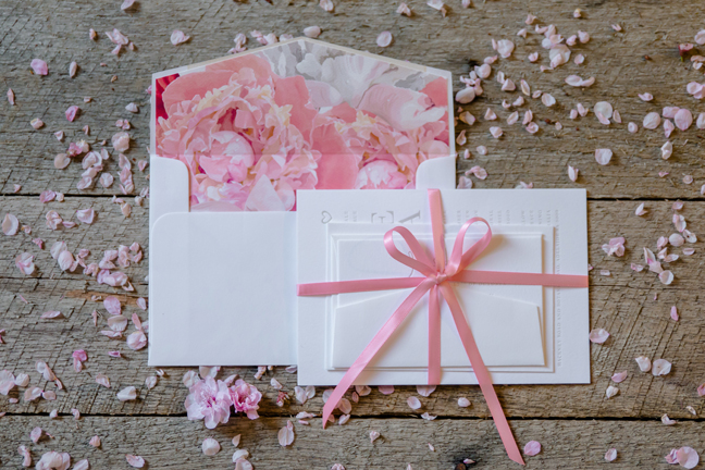 Pink ribbon wrapped around invitation suite with coordinating colours