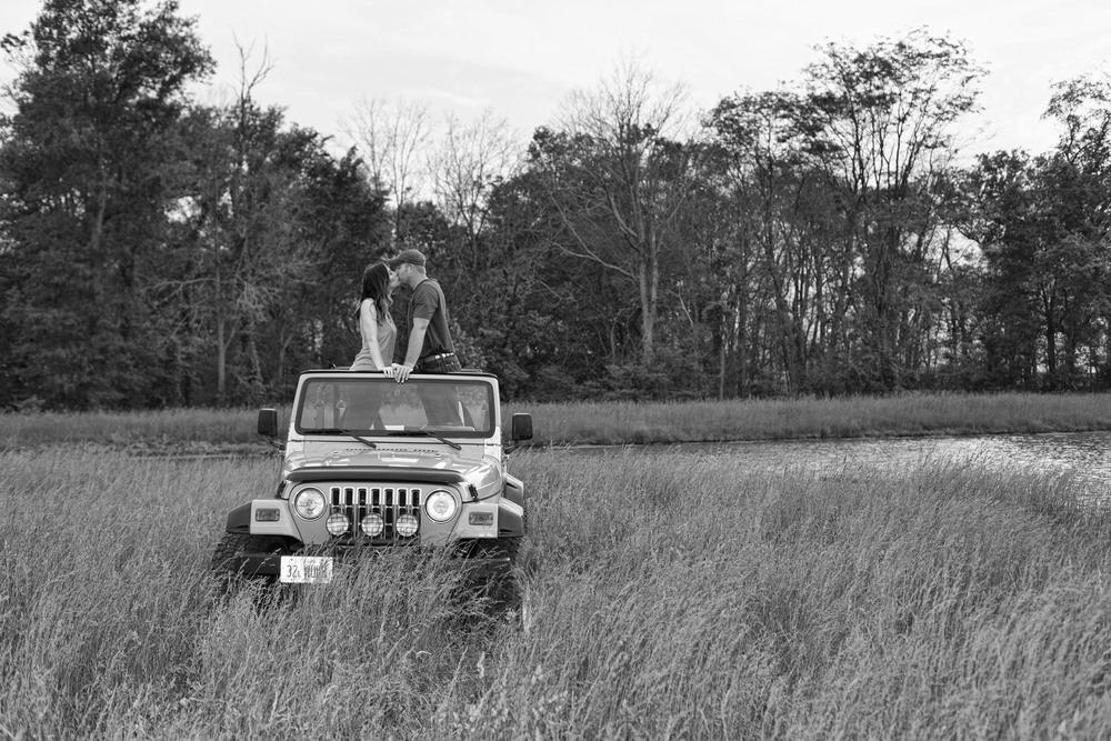couple-standing-on-jeep-black-and-white