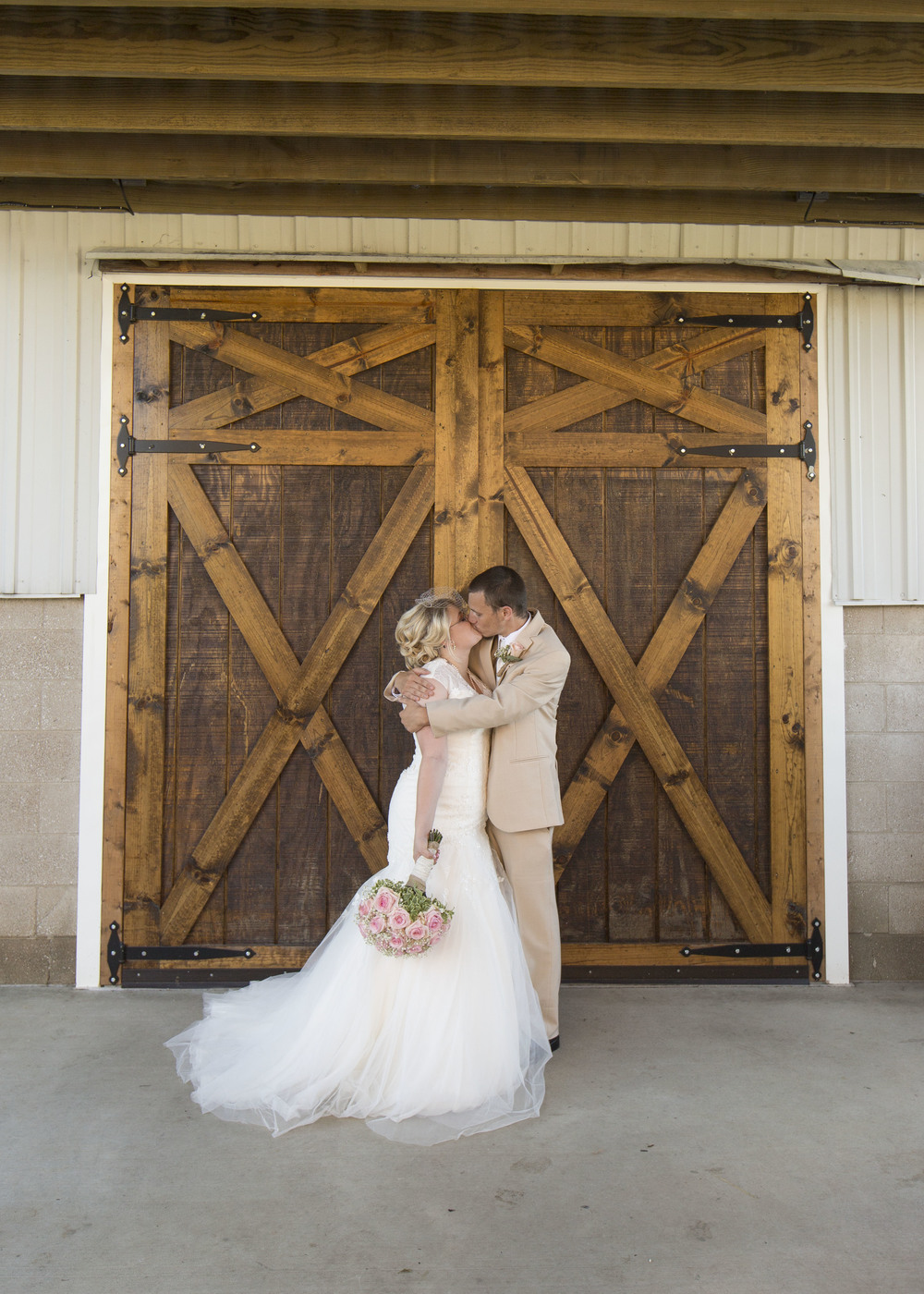 couple-in-front-of-barn-doors
