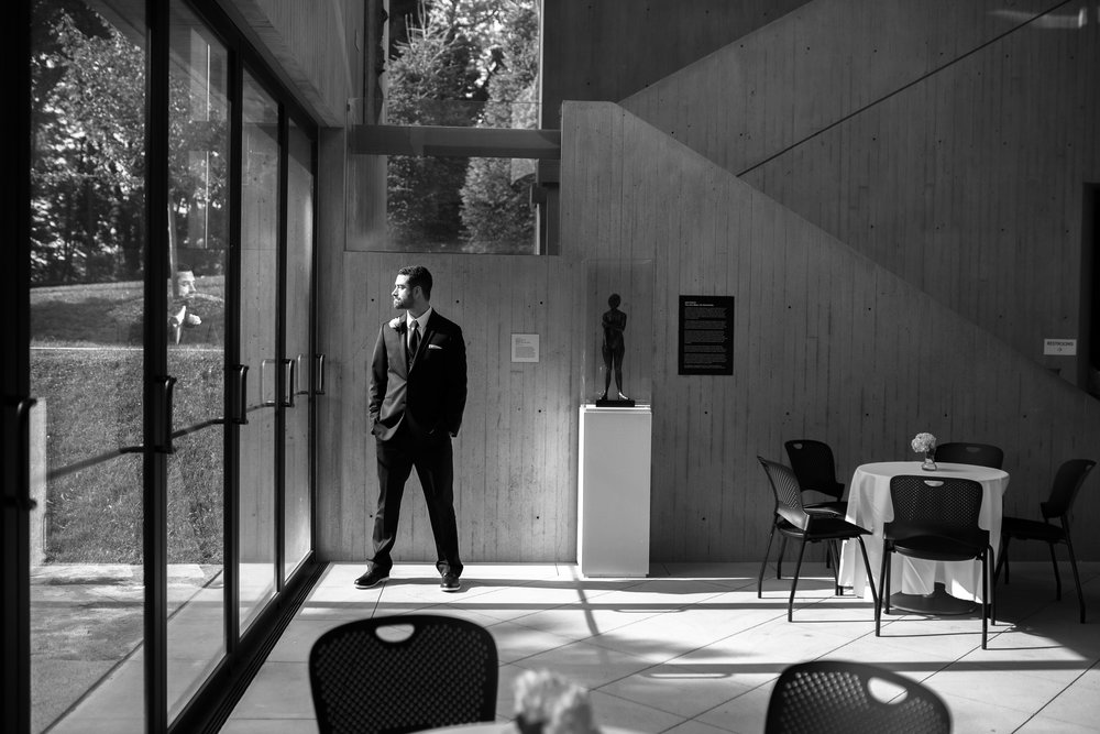 Tim, waiting for the ceremony to begin. I love the lines, the light, the reflection of his face on the glass and the sculpture beside him with a similar stance. It is also very special to me because Tim is the cousin closest to me in age. Shooting the wedding of someone you watched grow from a baby into a married man is honestly one of the best experiences I have had in photography.