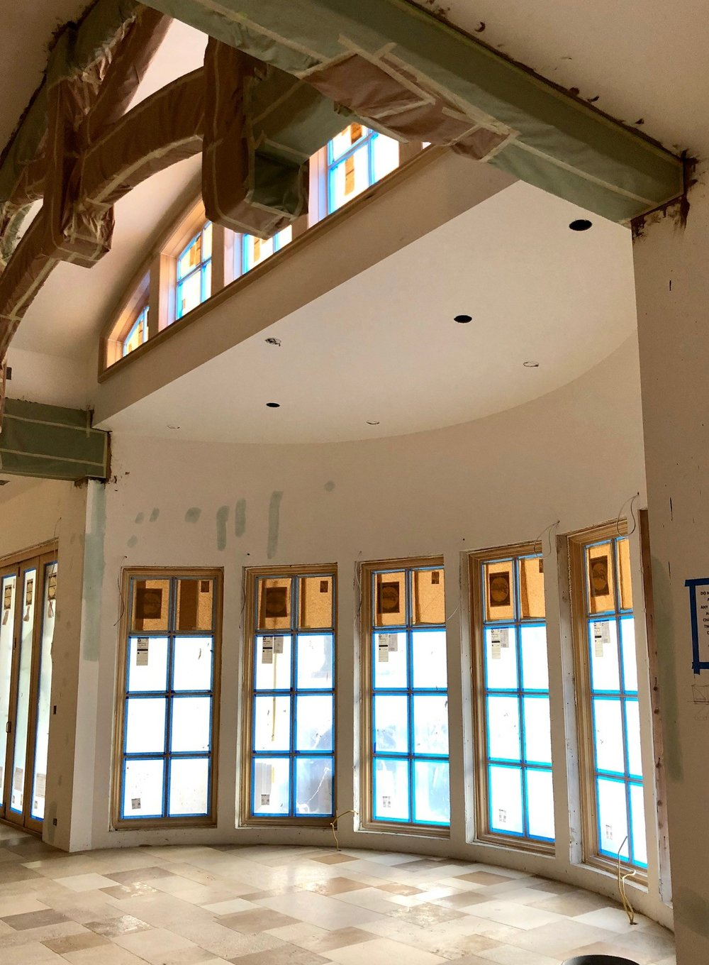 This shot captures both the antique limestone tile in the dining room as well as the beautiful beams and windows that are directly above it. The beams are still wrapped for protection during construction, but it's still a gorgeous set up in our opinion!