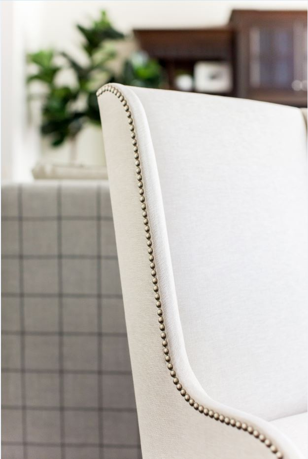 These two dining chairs are some of our favorites. We love the nailhead detail, which also makes an appearance in the family room you can see just beyond.