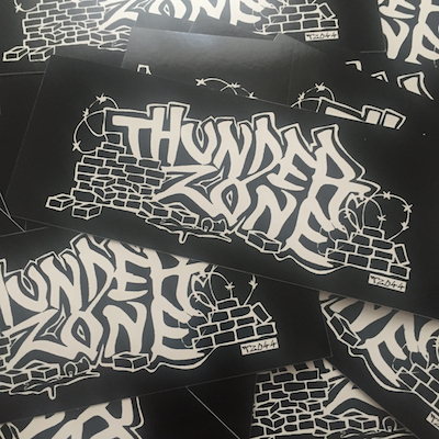"TZ044     THUNDER ZONE ""JUNKYARD STYLE"" STICKER    5.5 X 2.14 VINYL STICKER   EDITION OF 500   NOTES:  NEW STICKERS DESIGNED BY MIKE B AKA CITIBIKE MIKE AKA D. GOOKIN. BLACK VINYL. REPRESENT FOR ALL THE DIRTSTYLE JUNKYARD RAGERS JUST DOING THEIR BEST IN THIS INSANE WORLD. THUNDER ZONE: NEVER SURRENDER FOREVER.    BUY"