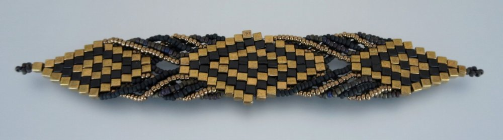 Symmetry: Intermediate Level. Taking brick stitch to the next level, with 4mm cubes stitched together to form a diamond which is connected by 11º seed beads, creates a mesmerizing bracelet.