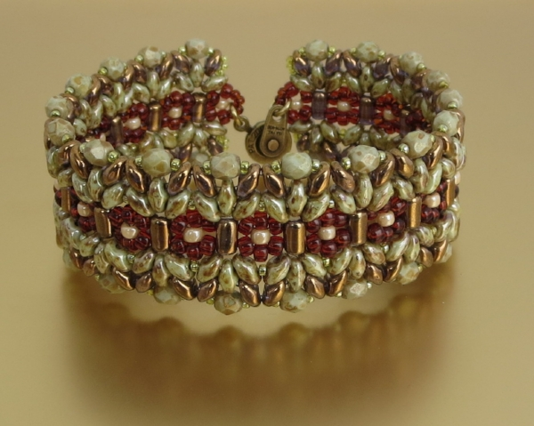 Florentine: Intermediate level. Rullas, Superduos, Firepolish, and seed beads united by right angle weave to create a wide, solid in appearance, bracelet. Project will be completed in class.