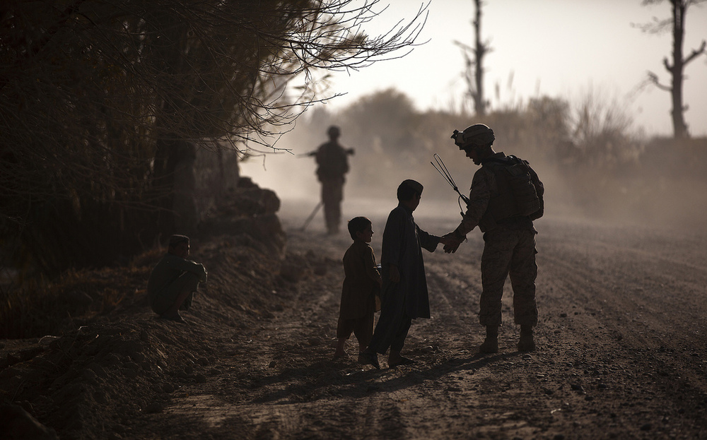 Marine Sergeant Jeremy Holsten, Lima 3/3, greets children while on patrol at Kuchiney Darvishan, Helmand province, Afghanistan, on 18 Dec 2011. Department of Defense photo, used in accordance with Creative Commons license.