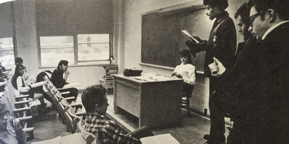 An activist flanked by supporters, addresses UW students in a classroom.