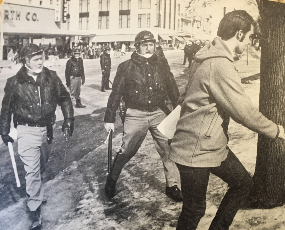 Riot police harass a young man – possibly a reporter – across the street from a Woolworth's store.