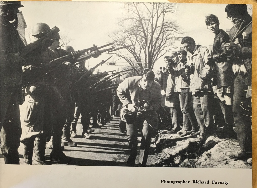 A man with a camera runs beneath the fixed bayonets brandished by a line of National Guardsmen standing opposite University of Wisconsin student protesters near Charter Street in Madison.