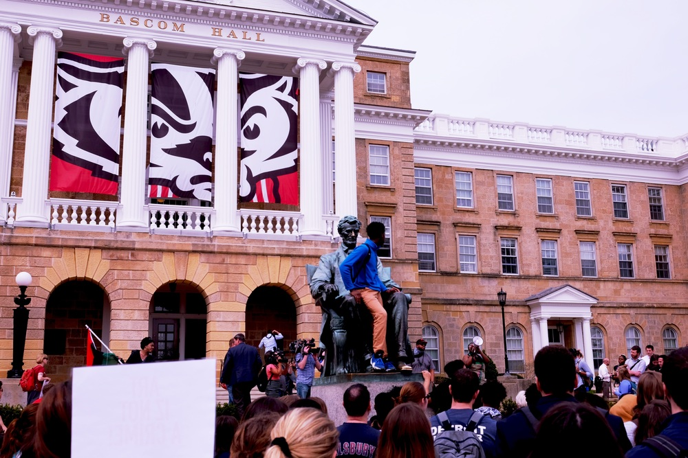 Students gathered at the Abe Lincoln statue on Bascom Mall listen to one of the organizers of the demonstration.