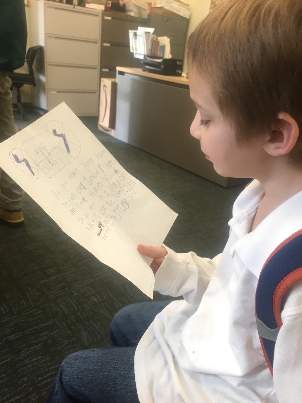 A student at Maury Elementary School reads an afternoon energy announcement that he composed.