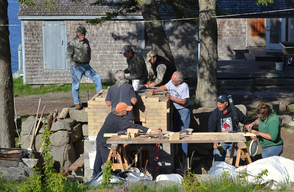 Pat Manley helps masonry workshop participants lay the last of the fire brick over the arched roof of the oven.