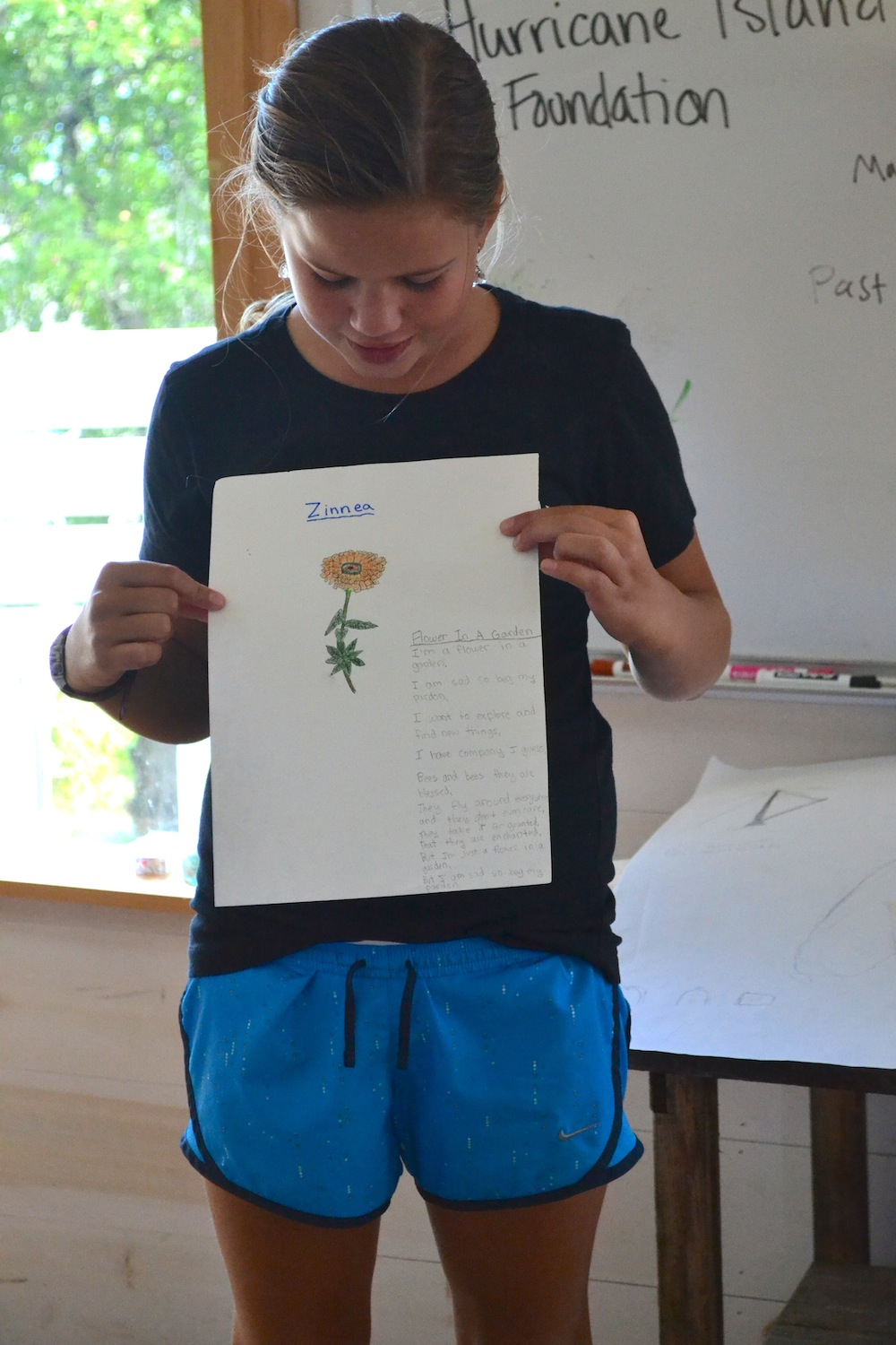 A student shows a drawing and poem she composed for her final project as part of the 2014 Living on the Edge program