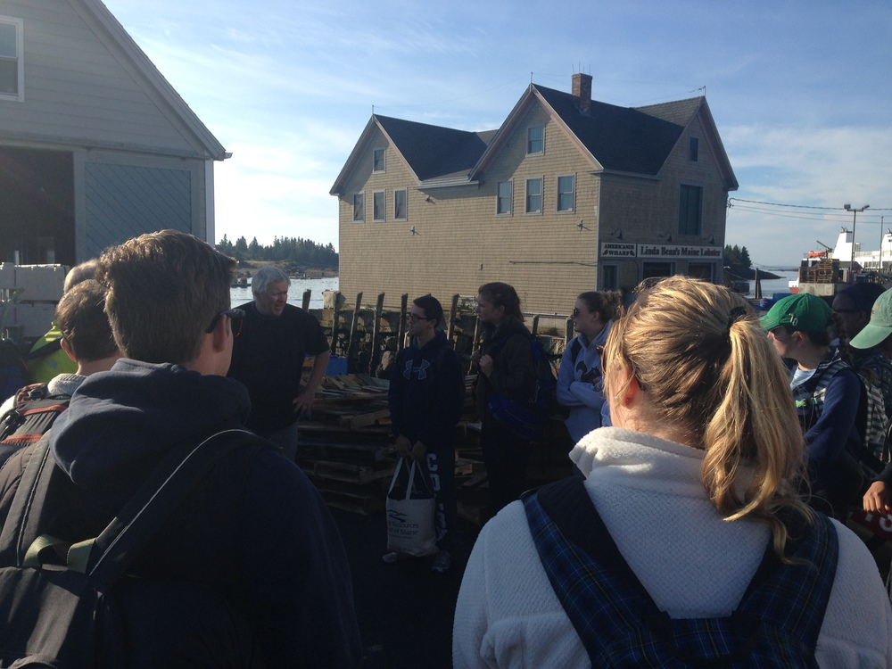 Colby students gather outside the Vinalhaven Co-op to learn more about the operation and the fishery from Mike Mesko.