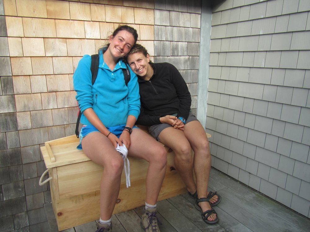 Science Educator, Isabelle, and Teaching Assistant, Lilla, sitting on the finished worm composting bench on the back deck by the galley.