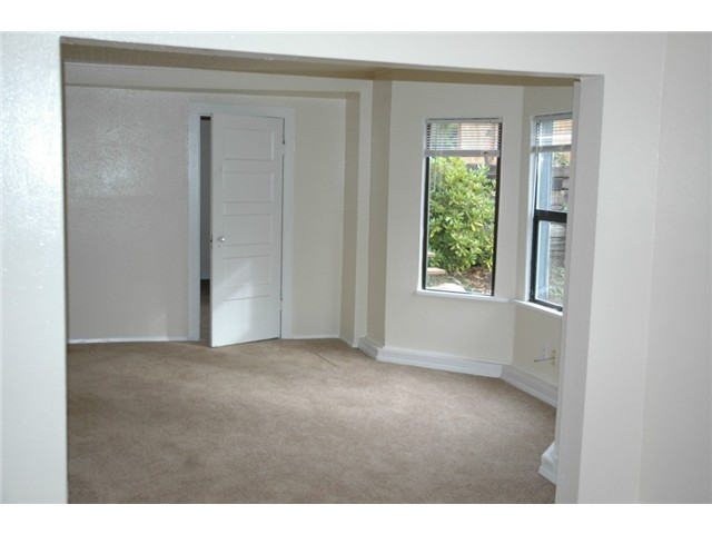 Dining room in the lower unit. Looking from the LR, 1 bedroom is thru the door in pic, the other 2 are around the corner to the left past the wall. Kitchen is to the left of the photographer. Nice light filled unit with direct access to back yard.