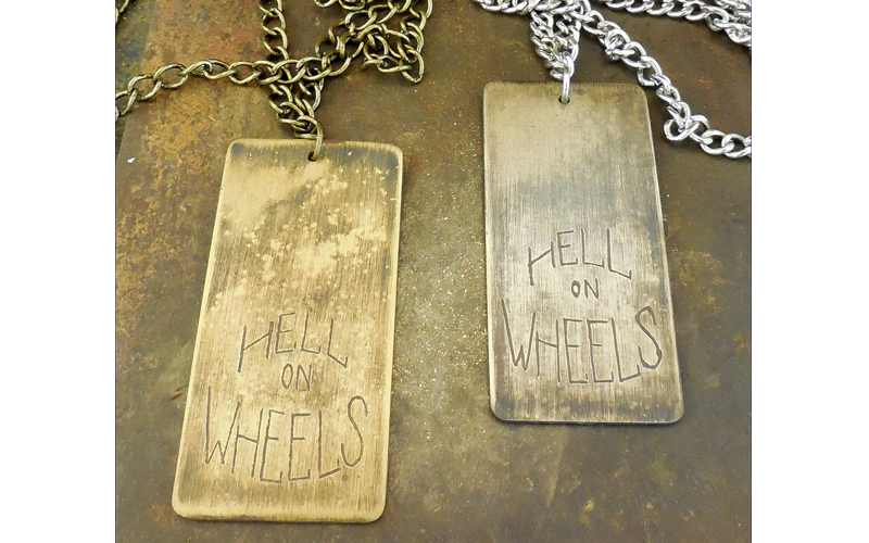 """L : Brushed brass Dog Tag with hand etched """"Hell on Wheels"""" on a brass chain. / $60  R :  Brushed silver Dog Tag with hand etched """"Hell on Wheels"""" on a silver chain. / $60"""