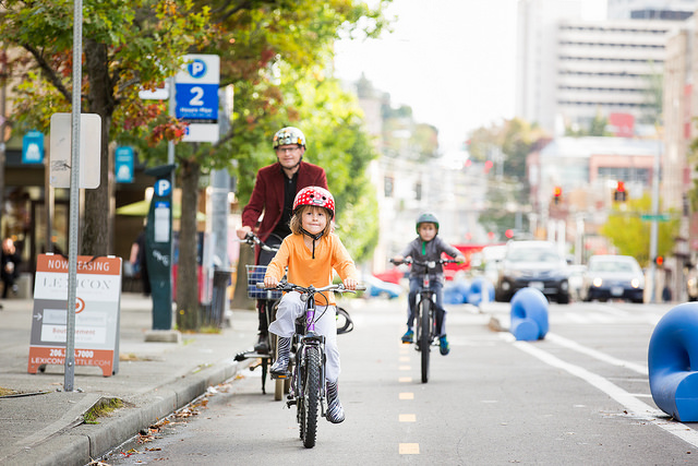 Two children bike in a cycletrack in Seattle. Soon children will be able to bike in a protected bike lane along Roland Avenue here in Baltimore. Photo Credit: Adam Coppola Photography