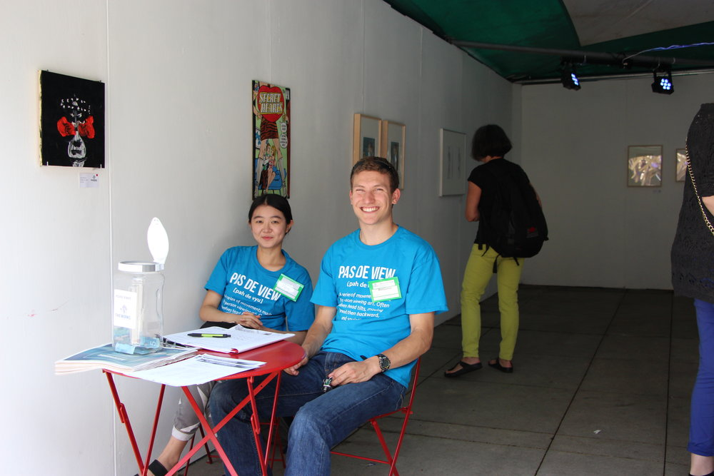 Two volunteers sitting in an art exhibit, The Best of the Cabinet of Queeriosities, 2016.