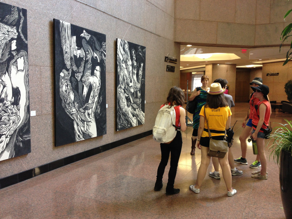 Interns discussing Jill Stanton'sWhat Good Are These? exhibit in Scotia Place on the Curatorial Interpretation tour during Festival.