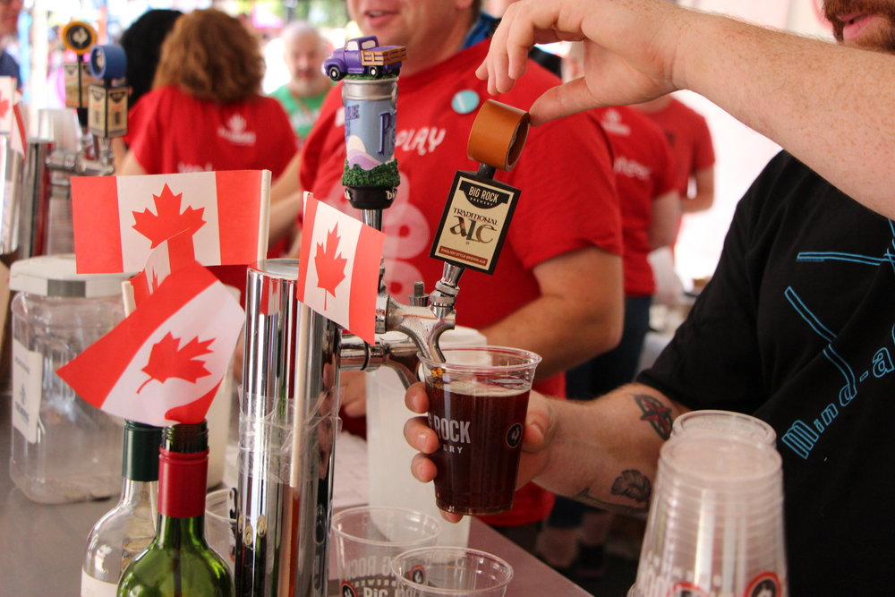 A volunteer serves beer at The Works Patio on Canada Day, 2017.