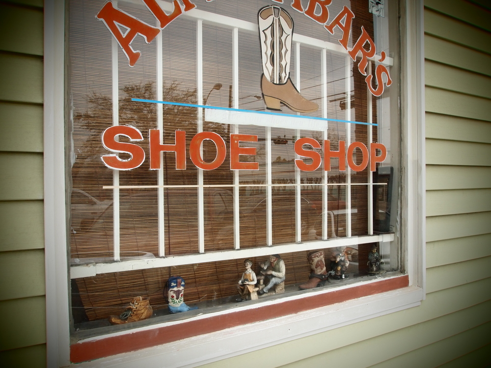 The charming Shoe Repair shop that has Hummel figurines in its window..