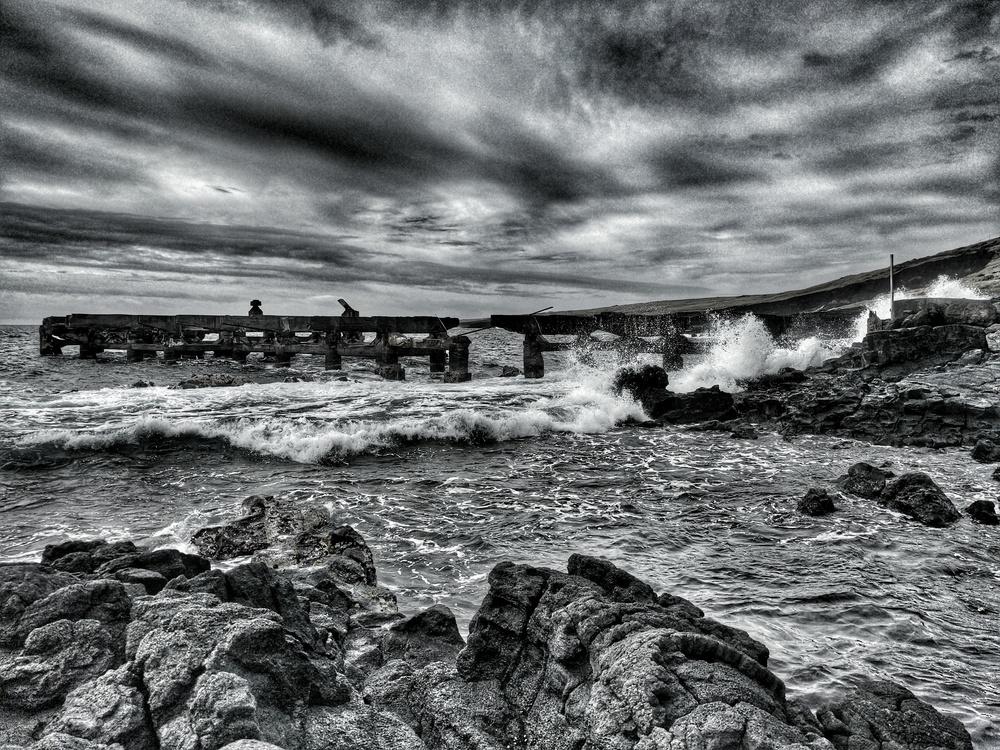 Waves crash against an old pier at Whittington Park