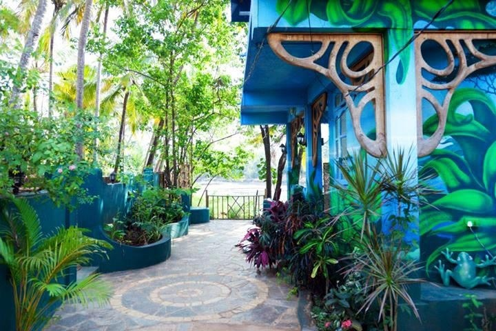 View of landscaping and artwork outside main hotel building of The Mandala Goa