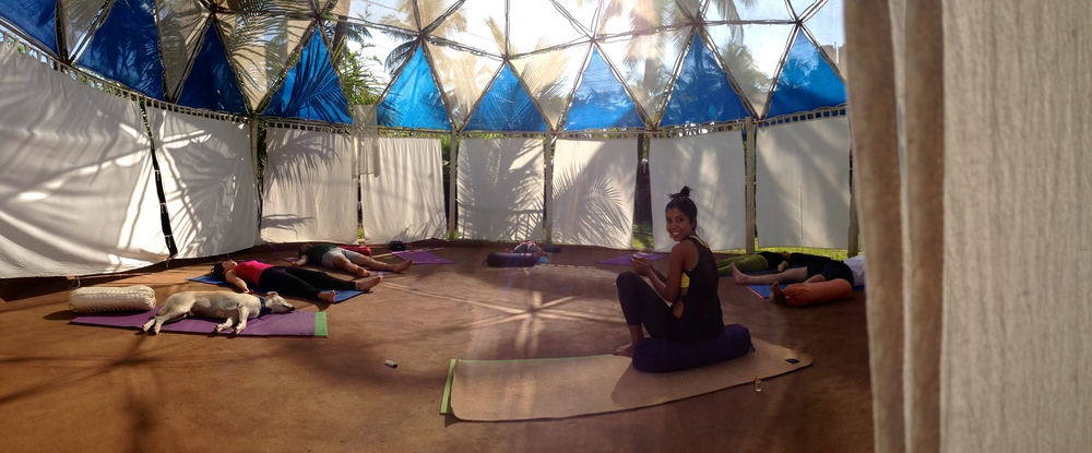 A TEACHER AT THE END OF A CLASS WITH HER STUDENTS IN SHAVASANA AT THE MANDALA YOGA-DOME