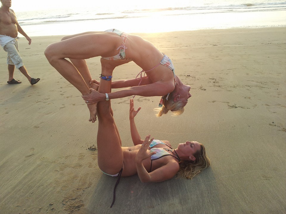 JENNY LIFTING A STUDENT INTO CLOSED-BRIDGE POSE IN AN ACRO YOGA SESSION